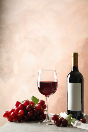 Grape, bottle and glass with wine on grey background, space for text