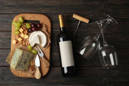 Bottle of wine, glasses, cheese and fruits on wooden background, top view