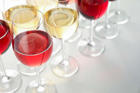 Glasses with different wine on white background, close up