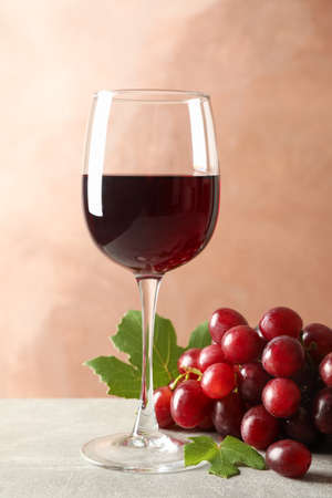 Grape and glass with wine on grey background, space for text Standard-Bild - 130571961