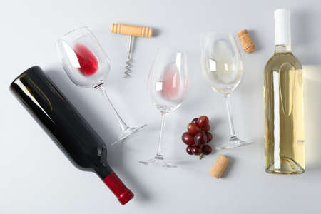 Flat lay. Grapes, corkscrew, bottles and glasses with wine on grey background