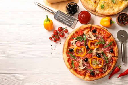 Delicious pizza and ingredients on white wooden background, copy space
