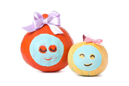 Pumpkins with facial mask and bow isolated on white background
