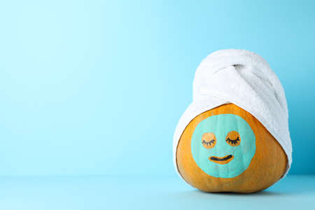 Pumpkin with facial mask and towel on blue background, copy space Standard-Bild