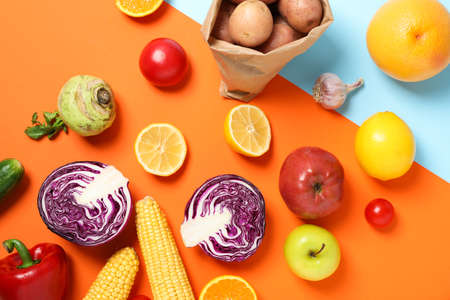 Different vegetables and fruits on two tone background, space for text