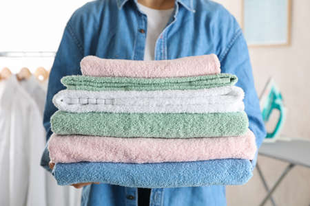 Young woman hold clean towels, close up and space for text