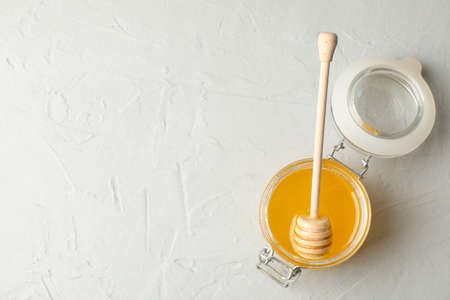 Glass jar with honey and dipper on white background, top view