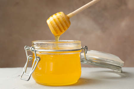 Glass jar with honey and dipper on white background, close up