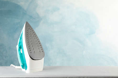 Iron on ironing board against blue background, space for text