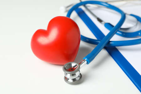 Stethoscope and heart on white background, close up