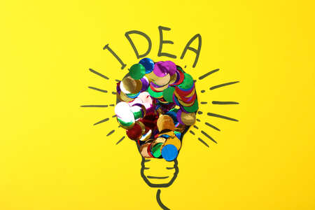 Drawn light bulb and multicolor glitter on yellow background. Good idea concept