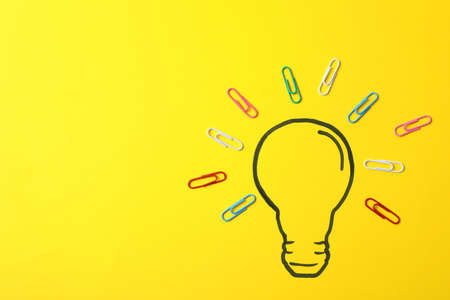 Drawn light bulb and clips on yellow background. Good idea concept Banco de Imagens