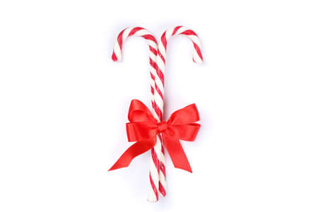 Sweet candy canes with bow isolated on white background