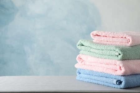 Pila di asciugamani puliti sull'asse da stiro, copia spazio
