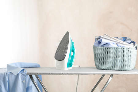 Iron and basket with clear laundry against light background, space for text