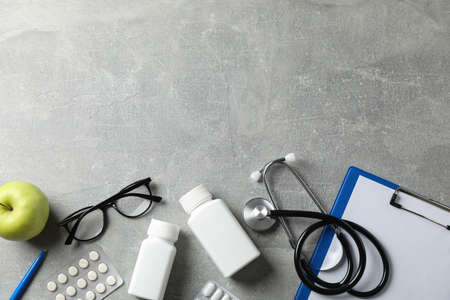 Stethoscope and medicines on grey background, top view. Doctor workplace Stok Fotoğraf