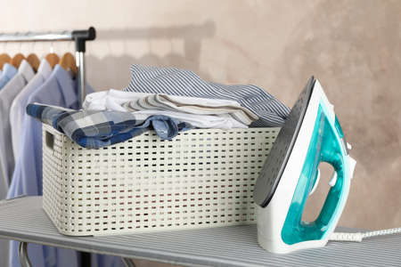 Basket with clean laundry and iron on ironing board, space for text