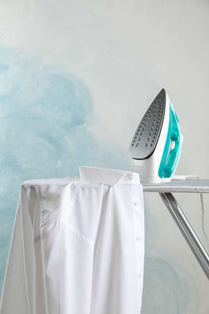 Iron and shirt on ironing board, space for text Stock Photo