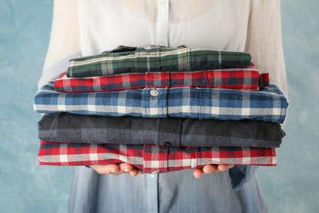 Female person hold folded shirts, close up Reklamní fotografie