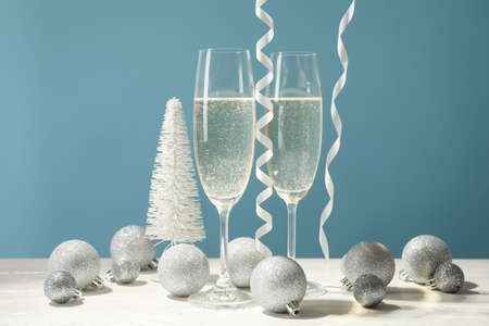 Champagne glasses and baubles against blue background, space for text