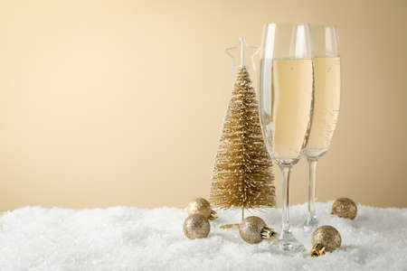 Champagne glasses and baubles against beige background, space for text