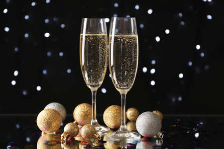 Christmas baubles and champagne glasses on blurred background, copy space
