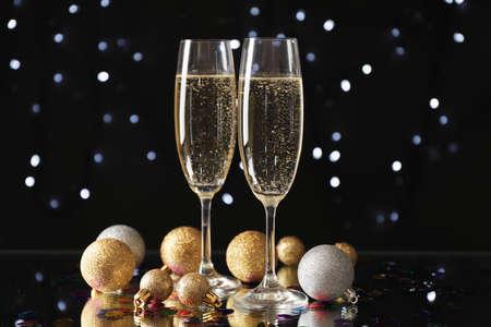 Palline di Natale e bicchieri di champagne su sfondo sfocato, spazio copia
