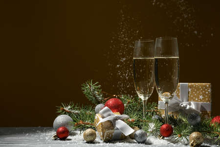Champagne glasses and baubles against golden background, space for text Reklamní fotografie