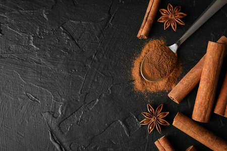 Cinnamon sticks, anise and spoon on black background, space for text