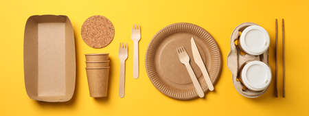 Flat lay with eco - friendly tableware on yellow background, space for text