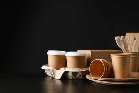 Eco - friendly dishware and carton box on black background, space for text