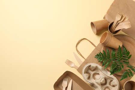 Composición con vajilla ecológica y planta sobre fondo beige, espacio para texto
