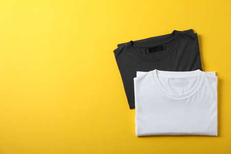 Folded blank t-shirts on yellow background, space for text
