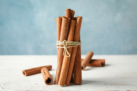 Cinnamon sticks on white wooden background, space for text
