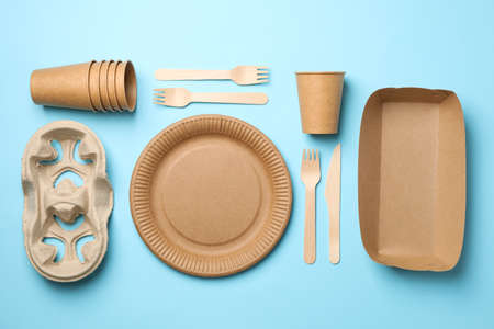 Flat lay with eco - friendly tableware on blue background, space for text