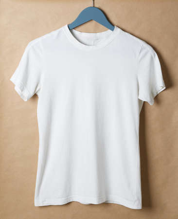 Hanger with blank white t-shirt on cardboard background, space for text