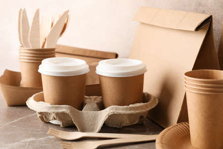 Eco - friendly tableware and paper bag on grey table, close up