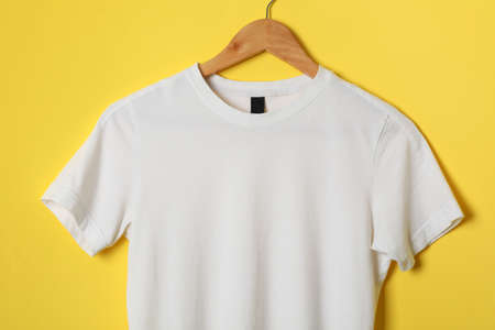Hanger with blank white t-shirt on yellow background, space for text
