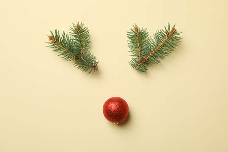 Reindeer face made of fir branches and bauble on beige background, space for text