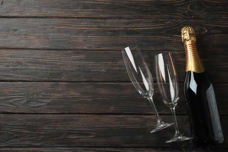 Champagne glasses and bottle on wooden background, space for text