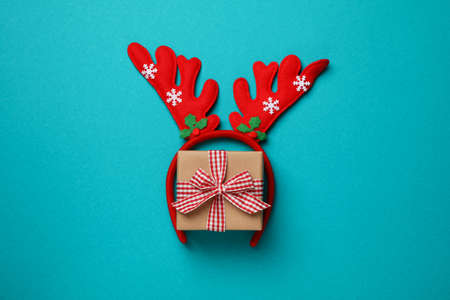Red deer horns and gift box on turquoise background, space for text 版權商用圖片