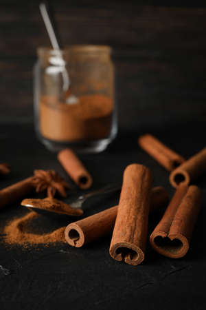 Cinnamon sticks, spoon and glass jar with powder on black background, space for text