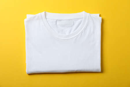 Folded blank white t-shirt on yellow background, space for text