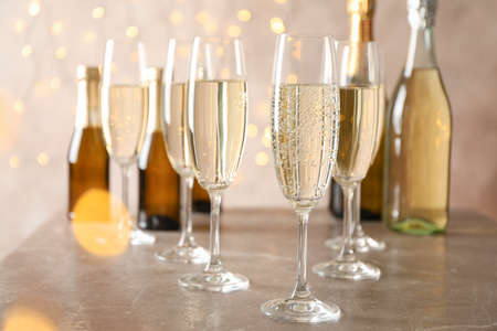 Champagne glasses and bottles on decorated background, space for text 版權商用圖片