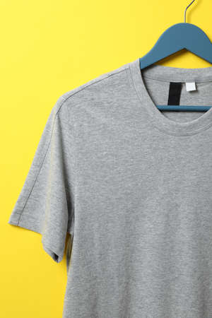 Hanger with blank gray t-shirt on yellow background, space for text 版權商用圖片
