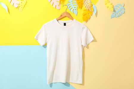 Hanger with blank white t-shirt on multicolored background, space for text