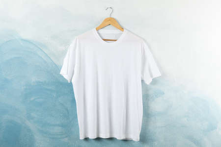 Hanger with blank white t-shirt on blue background, space for text