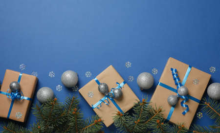 Gift boxes, pine branches and Christmas balls on blue background, space for text