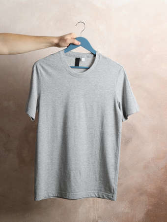 Man holds a hanger with blank gray t-shirt on brown background, space for text