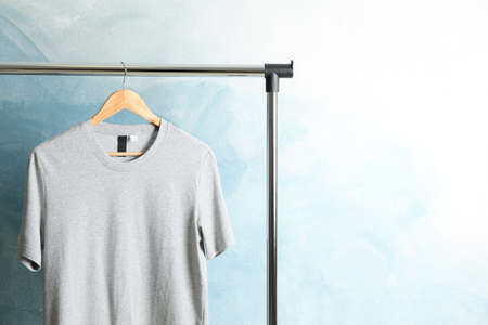 Rack with blank gray t-shirt on blue background, space for text